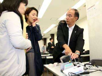 キャッシュレス端末の使い方の説明を受ける土屋さん(左)と三浦さん(中央)