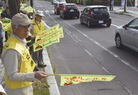 ドライバーらの目を引く黄色の旗を掲げ、交通安全を促す啓発参加者=幌別小学校前