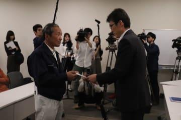 浦瀬課長(右)に申し入れ書を手渡す炭谷代表=県庁
