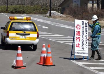 通行止めの看板を設置する作業員=10日午前9時30分ごろ、福島市