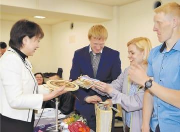 ベラルーシ選手団から同国の特産品をプレゼントされる郡市長(左)