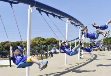 北九州市の響灘緑地グリーンパークに新設された、全長約163メートルのブランコを楽しむ児童ら。世界一長いブランコとしてギネス認定された=11日午後