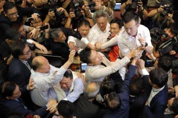 11日、香港立法会でつかみ合う民主派議員と親中派議員(AP=共同)