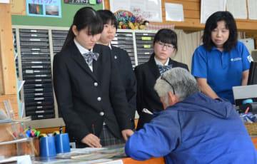 高千穂町中心部の観光案内所でボランティア活動を行う、甲斐眞陽さん(左端)ら高千穂高生