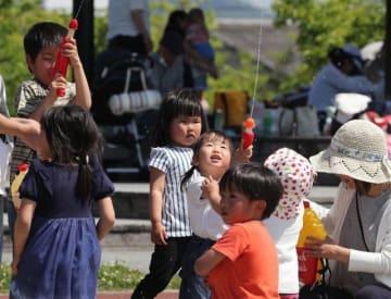 陽気の下、水鉄砲で遊ぶ子どもたち=11日午後1時58分、岡山市南区浦安西町