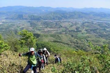 雄大な蒜山高原の景色をバックに山頂を目指す登山客=中蒜山9合目付近
