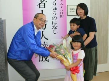 1万人達成記念の花束を受け取る本多さん親子(右)=11日、日田市のアオーゼ