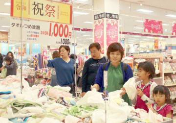 タオルの袋詰めコーナーに集まる買い物客=1日、大分市のイオンパークプレイス大分店