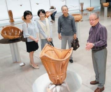 アートプラザで始まった生野徳三作品展。鑑賞者に作品の説明をする生野徳三さん(右端)=11日、大分市荷揚町