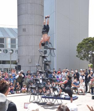 組み上げたパイプ椅子の上で逆立ちを披露する「Hiro&AG」=日立市幸町