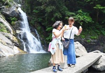 真夏日に迫る暑さの中、ソフトクリームを手に涼む親子連れ=唐津市相知町の見帰りの滝(撮影・鶴澤弘樹)