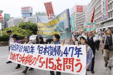 東京・新宿で、沖縄県名護市辺野古への基地移設反対などを訴えデモ行進する人たち=12日午後