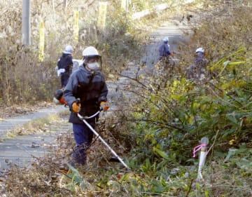 福島県葛尾村の「特定復興再生拠点区域」で草を刈る除染作業員=2018年11月