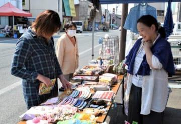 ハンドメイド品などが並ぶ朝市で品定めする客(左)