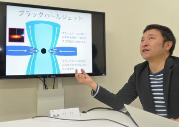 ジェットの解説用画像を映し「撮影されたブラックホールにジェットが写っていなかったのは意外」と話す大須賀健教授=つくば市の筑波大