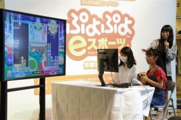 「eスポーツ」の体験会で、パズルゲーム「ぷよぷよ」の対戦を楽しむ参加者ら=12日、熊本市中央区のびぷれす広場