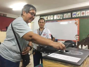 13日、マニラの投票所で票を投じる有権者(共同)