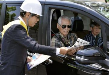 交通事故防止を呼び掛けるチラシを受け取るドライバー=13日、大津市