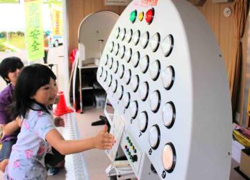 光るボタンを押して反射神経のチェックを受ける児童ら(大津市黒津4丁目・南郷水産センター)