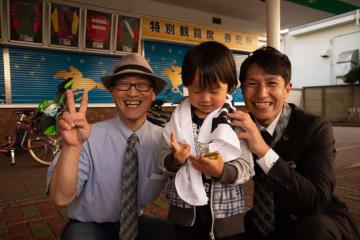 左側でピースされてるのが角居勝彦調教師、右側が大津剛調教師補佐