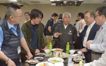 めいつ美々鯵の試食会で豊洲市場関係者らと意見交換する元浦会長(中央)