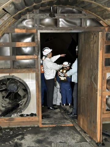 火災が鎮火した石炭博物館の模擬坑道出口付近を視察する関係者ら=13日午後、北海道夕張市