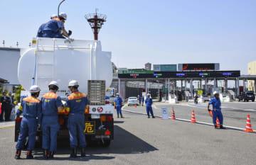 名神高速道路の吹田料金所で、危険物を運搬するタンクローリーを点検する消防職員ら=13日、大阪府吹田市