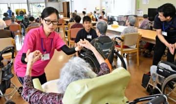 入所者とコミュニケーションを取りながら体操介助をするダマング・アイティマヤさん(左)=串間市西方の「幸せホームあすか」