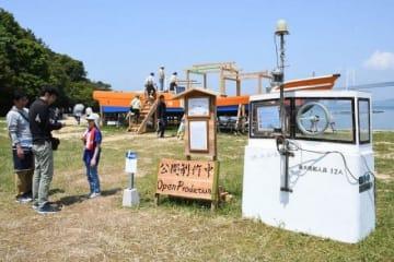 改装した漁船を用いたアートユニット「Yotta(ヨタ)」の作品を楽しむ人たち=5月3日、坂出市・沙弥島