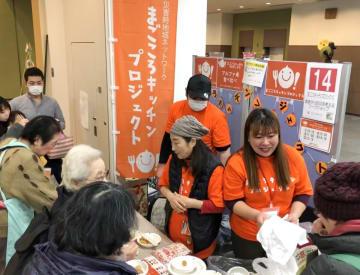 まごころキッチンプロジェクトのPRをする小野さん(右)=今年2月、川崎市中原区(同プロジェクト提供)