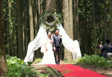 森の中の結婚式で指輪を披露する(右から)田島大輔さんと茉莉さん=12日、日田市中津江村