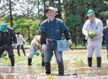 手で苗を植える農家ら