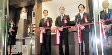 支店入り口であったセレモニーであいさつする田尾社長(右から2人目)と国分専務(同3人目)ら=13日、東京・日本橋