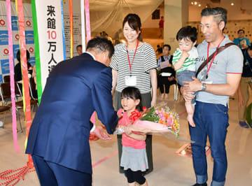 来館者10万人目となり、横戸長兵衛市長から花束を受け取る山田さん親子=上山市・めんごりあ