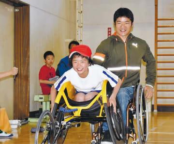 樋口選手に支えてもらい、競技用車いすを体験する児童