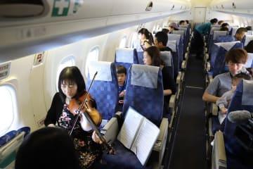 ORCの機体で空からの景色を楽しむ参加者ら=長崎県内上空
