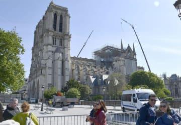 ノートルダム寺院を背に写真撮影する観光客ら=13日、パリ(共同)
