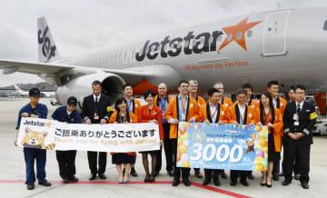累計搭乗者が3千万人に到達し、記念撮影するジェットスター・ジャパンの社員ら=14日午後、成田空港