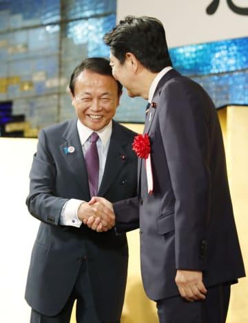 自民党麻生派の政治資金パーティーで安倍首相(右)と握手を交わす麻生副総理兼財務相=14日夜、東京都内のホテル