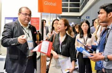 ブースを訪れた各国のバイヤー団に商品を説明するアスクレピオスの高橋CEO(左)=14日、HKCEC(NNA撮影)