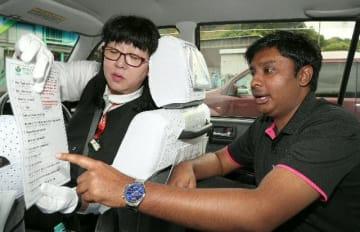 タクシー運転手に英会話マニュアルの使い方を教えるラジタ・サダルワンさん(右)=14日、大分市下郡のふたばタクシー