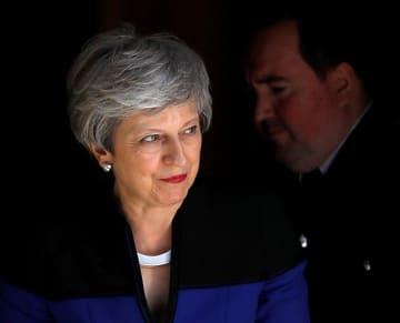 14日、ロンドンの首相官邸前に姿を見せたメイ英首相(ロイター=共同)