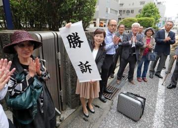 判決を受け「勝訴」の旗を掲げる原告側弁護士ら=長崎市万才町、長崎地裁前