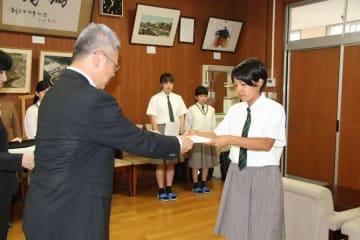 中村課長(左)から委嘱状を受け取る生徒=長崎商業高