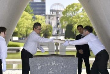 風通しのため、原爆慰霊碑下の石室から原爆死没者名簿を取り出す広島市の職員=15日午前、広島市の平和記念公園