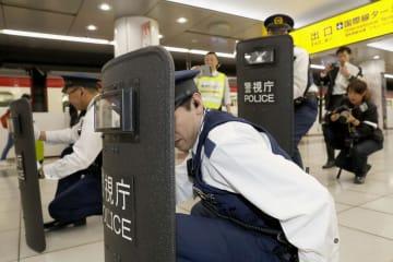 京急電鉄の羽田空港国際線ターミナル駅で行われたテロ対策訓練で、盾を持ち不審物に向かう警察官=15日午前