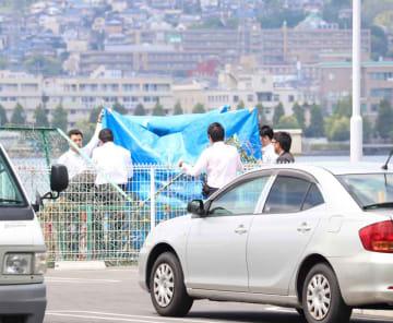軽乗用車が衝突したフェンスの前に運転手2人を立ち会わせて調べる捜査員(15日午前10時15分、大津市大萱6丁目)