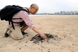 砂浜に放置された炭を片付ける粟野真造さん=西宮市西波止町