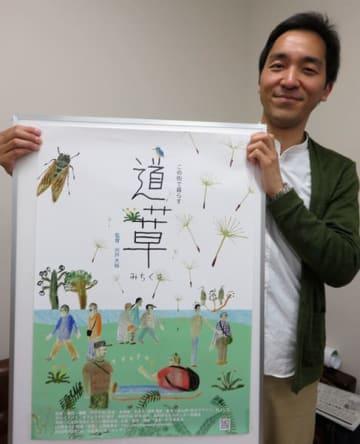【ドキュメンタリー映画「道草」のポスターを手にする宍戸監督=伊勢市役所で】