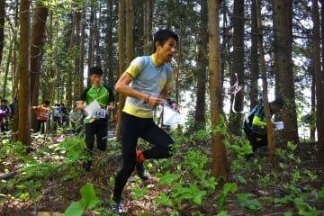 地図とコンパスを手に山林の中を駆ける参加者